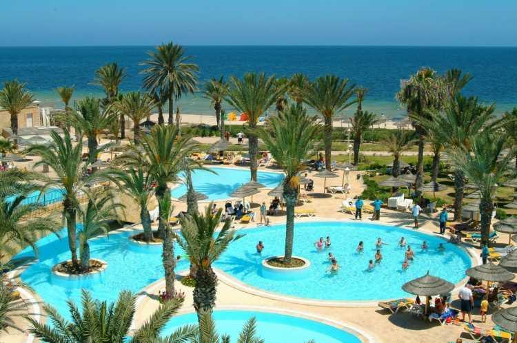 Bazény jsou mezi palmami u pobřeží moře
